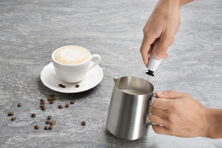 handheld milk frother in jug with cappuccino