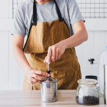 man using manual milk frother