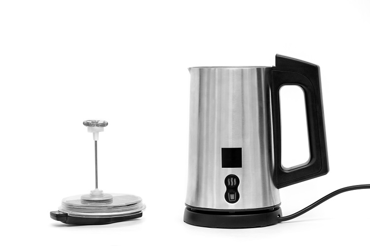Automatic milk frother. The frother is made of stainless steel with a black plastic top, handle, buttons and power cord