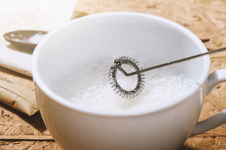 frothy milk in cup with handheld milk frother whisk