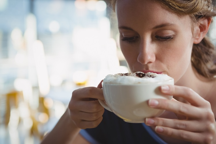 young woman drinking frothy coffee made with vegan barista blend milk