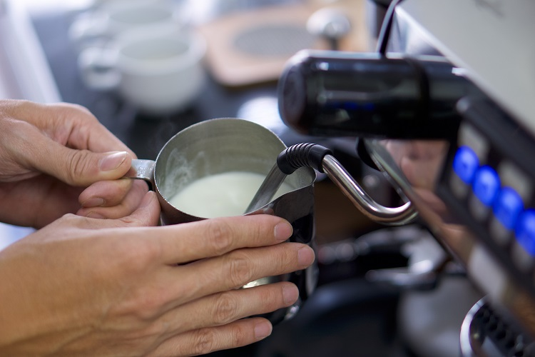 Barista holding pitcher full of milk frothing in the cappuccinatore of coffee machine