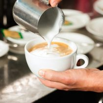 Barista making cappuccino and pouring frothy milk from milk pitcher