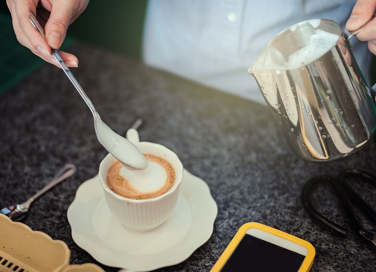Barista making cappuccino coffee and pour milk frother for topping