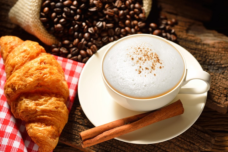 cup of cappuccino with coffee beans and croissant