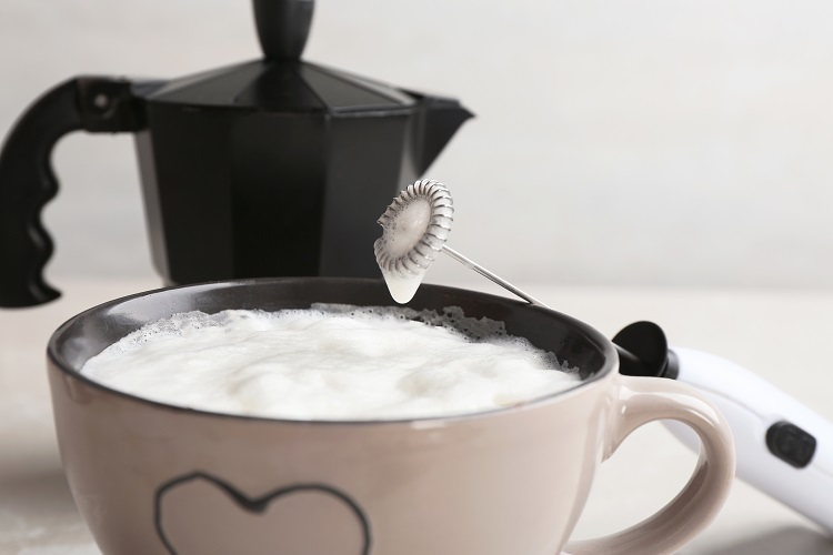 stovetop milk frother and cup of frothy coffee and handheld milk frother